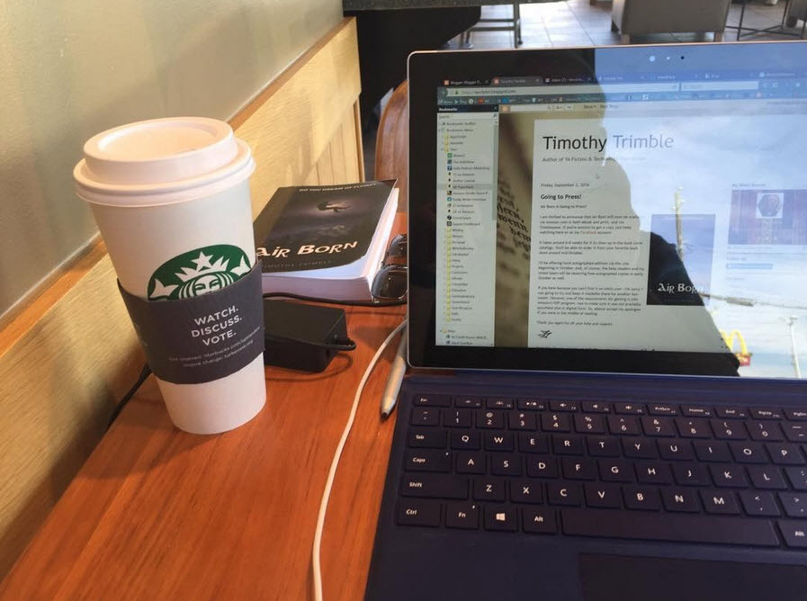 iPad, coffee, and book on a table at Starbucks.